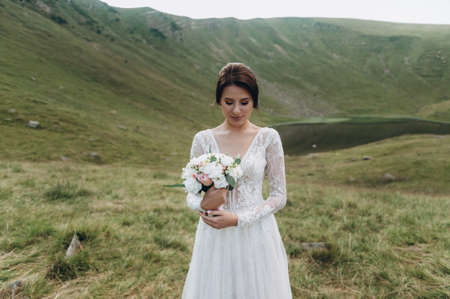bride with a bouquet of flowers stands against the lake in the mountains