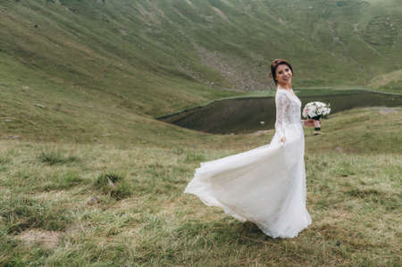 The bride in the mountains near the lake. The bride is wearing a long wedding dress with lace and an open back