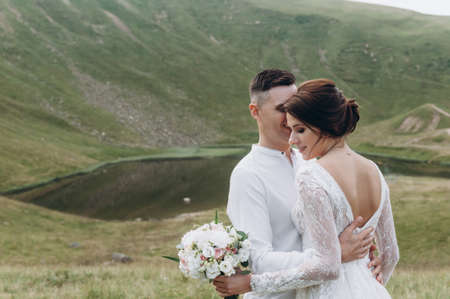 Bride and groom hug each other tender standing on the golden hill. Archivio Fotografico