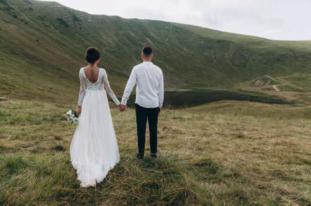 The bride and groom hold hands against the backdrop of mountains. Copy space