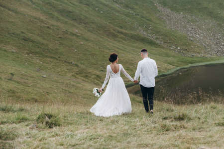 Scenic mountain view. Beautiful young wedding couple of groom and bride walking on the mountain