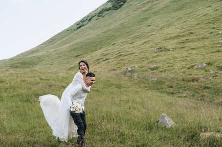 the bride and groom have fun and laugh against the backdrop of a mountain landscape Archivio Fotografico
