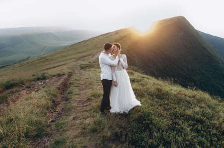 newlyweds kissing in the mountains. Wedding in the mountains at sunset