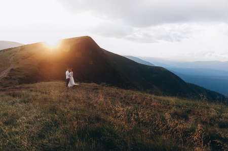 Newlyweds stand hugging against the background of the mountains at sunset