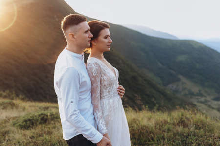 Newlyweds stand hugging against the backdrop of the mountains