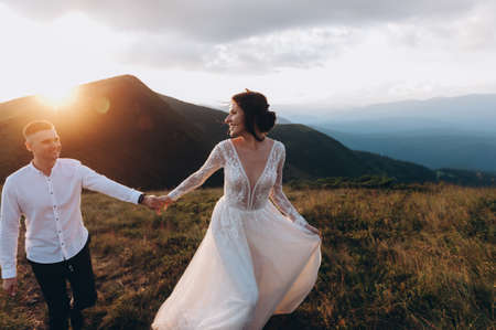 Walking with a mountain lawn. Carpathian Mountains in the background. follow me photo. Newlyweds on the wedding day.
