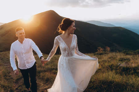 bride and groom on a wedding walk in the mountains during sunset
