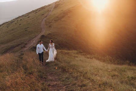 Bride and groom walk hands on mountain road at sunset
