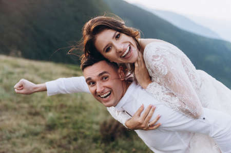 Happy newlyweds in funny poses against the backdrop of the mountains Archivio Fotografico