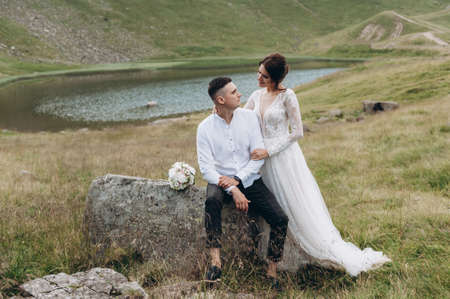 bride and groom on the mountain. Groom sitting on the rock Archivio Fotografico