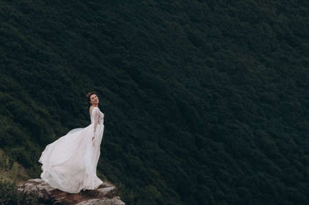 the bride stands on a rock in the mountains. Wind develops white bride dress Archivio Fotografico