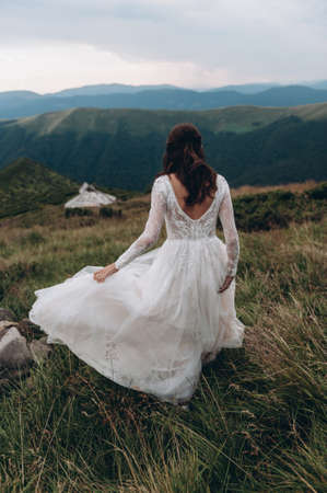 Bride backs walks on lawn in the mountains Archivio Fotografico
