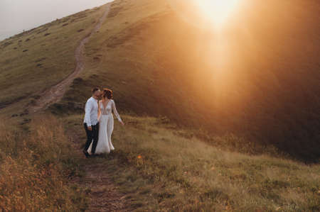 newlyweds kiss at sunset in the mountains Archivio Fotografico