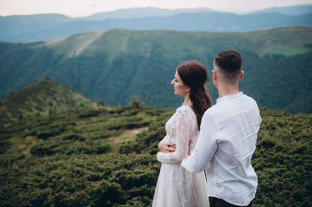 The young bride leans on a stylish groom and stands. A newlywed couple hugging outdoors at nature Archivio Fotografico