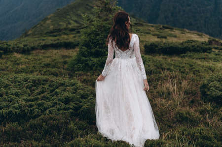 Bride in white dress stands back in the mountains Archivio Fotografico