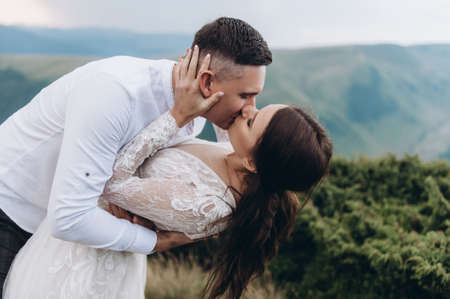 Wedding, Beautiful Romantic Bride and Groom Kissing and Embracing in the mountans