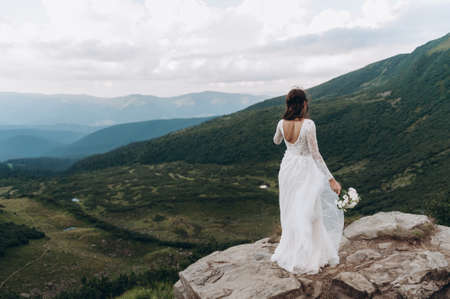 Bride with a bouquet of flowers in a white dress stands on a rock