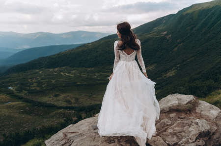 the bride stands on a rock in the mountains. Wind develops white bride dress