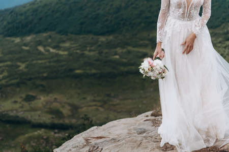bouquet of unsold. Bride in white dress in the mountains