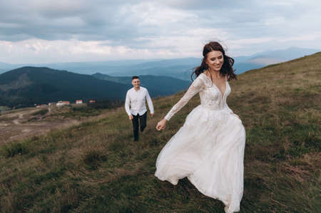 Running away from her groom. Wedding day in the mountains Archivio Fotografico