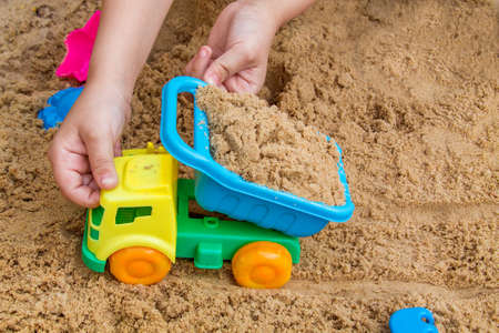 child playing in the sandbox on a summer day