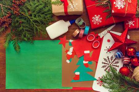 preparation for Christmas. The child makes a paper card, packaging gifts. Stockfoto