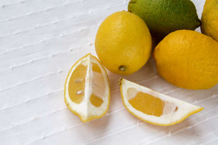 Mature and immature lemons lie on white cloth Stock fotó