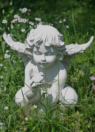 Garden statue of angel holding the dove Stock Photo
