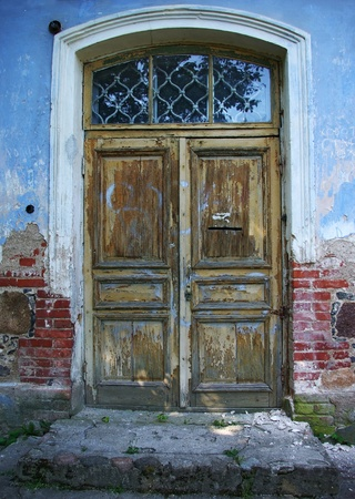old building facade: View on the old wooden door of abandoned house