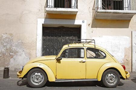 escarabajo: Vendimia amarillo VW Beetle en la calle de Puebla, México Editorial