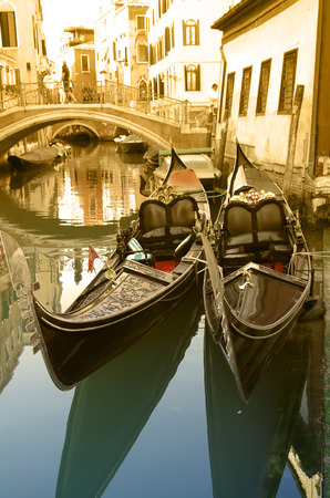 Gondolas mooring along canal - typical view at Venice, Italy photo