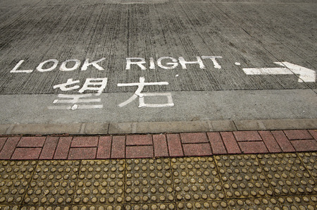 look at right: Bilingual (English and Chinese) Look right road sign on pedestrian cross of Hong Kong