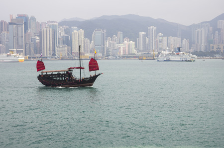 HONG KONG - FEBRUARY 25: The junk boat  in Victoria harbor on February 25, 2013 in Hong Kong. A red chinese traditional junk boat, Aqua Luna, is one of famous tourist attraction