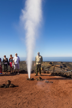 timanfaya: LANZAROTE, CANARY ISLANDS - JANUARY 07, 2014: Tourists on the geyser of steam show of the Timanfaya. It is one of the main attractions of Timanfaya national park, Lanzarote, Canary Islands, Spain Editorial