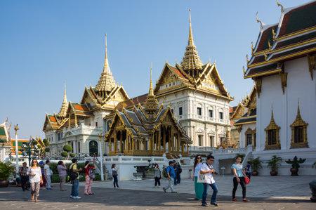stupas: BANGKOK, THAILAND - JANUARY 24, 2015: Unidentified tourists visit the Grand Palace in Bangkok, Thailand. Grand Palace in Bangkok is the most famous landmark of Thailand