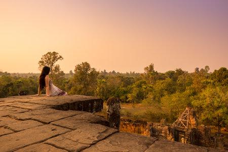 mujer mirando el horizonte: Angkor Wat, Camboya - 28 de enero, 2015: Mujer hermosa joven que ve la puesta de sol en la parte superior de Phnom Bakheng en Angkor, Camboya