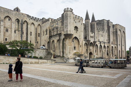 largest: AVIGNON, FRANCE - MAY 04, 2015: Tourists on the square of Popes Palace Avignon. Popes Palace is the main historical site in Provence and one of the largest and most important medieval gothic buildings in Europe Editorial