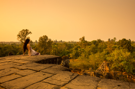 mujer mirando el horizonte: ANGKOR WAT, CAMBODIA - JANUARY 28, 2015: Young beautiful woman watching sunset at the top of Phnom Bakheng at Angkor, Cambodia