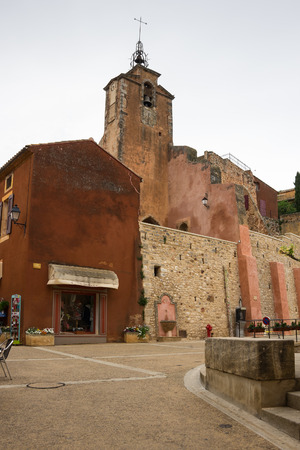 ochre: ROUSSILLON, FRANCE - MAY 03, 2015: Street of medieval village of Roussillon. It ochre village is included in list of The most beautiful villages of France
