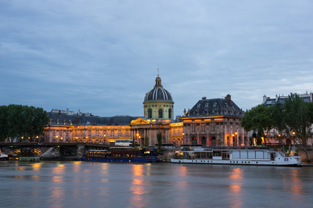 academie: PARIS, FRANCE - MAY 07, 2015: The French Institute and Pont des Arts across the Seine river at night, Paris, France. The Institut de France ( French Institute) is a French learned society, grouping five academies, the most famous of which is the Academie