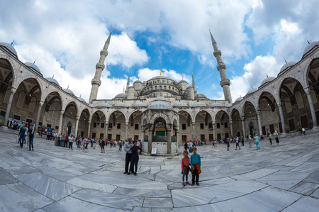 adorning: ISTANBUL, TURKEY - JUNE 19, 2015: People visiting Sultan Ahmet Mosque (Turkish: Sultan Ahmet Camii), a historic mosque in Istanbul, Turkey. The mosque is popularly known as the Blue Mosque for the blue tiles adorning the walls of its interior