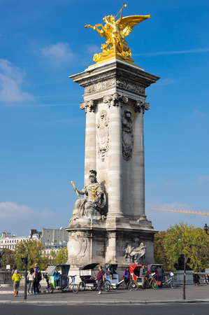 PARIS, FRANCE - OCTOBER 11, 2015: Gilded Fames sculptures on the socle counterweights of Pont Alexandre III over the river Seine in Paris, France
