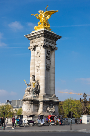 socle: PARIS, FRANCE - OCTOBER 11, 2015: Gilded Fames sculptures on the socle counterweights of Pont Alexandre III over the river Seine in Paris, France