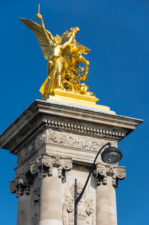 Gilded Fames sculptures on the socle counterweights of Pont Alexandre III over the river Seine in Paris, France