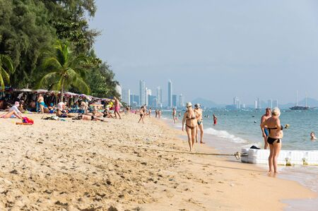 PATTAYA, THAILAND - JANUARY 29, 2017: People relaxing on the beach of Pattaya, a resort city in Thailand on the east coast of the Gulf of Thailand