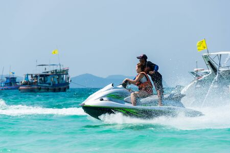 PATTAYA, THAILAND - FEBRUARY 02, 2017: Tourists skiing on water scooter on the beach of Ko Lan island in the Gulf of Thailand near Pattaya, Thailand Редакционное