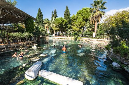 PAMUKKALE, TURKEY - OCTOBER 26, 2017: People swimming and enjoying the thermal water in Cleopatras pool in Pamukkale, Turkey