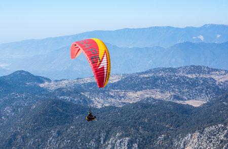 KEMER, TURKEY - OCTOBER 22, 2017: Paraglider flying over mountains near Kemer, a seaside resort on the Turkish Riviera in Antalya Province, Turkey