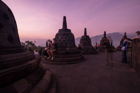 JAVA, INDONESIA - 09 SEPTEMBER 2018: Tourists watching sunrise at Borobudur, a 9th-century Mahayana Buddhist temple in Central Java, Indonesia. The monument is the most visited tourist attraction in Indonesia 新闻类图片
