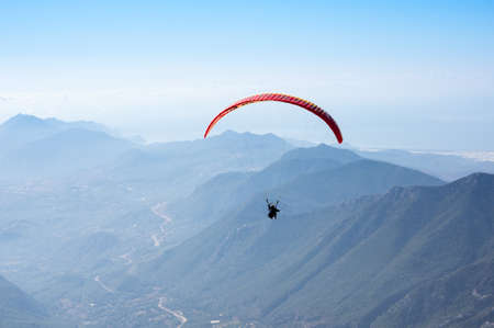 Paraglider flying over mountains near Kemer, a seaside resort on the Turkish Riviera in Antalya Province, Turkey